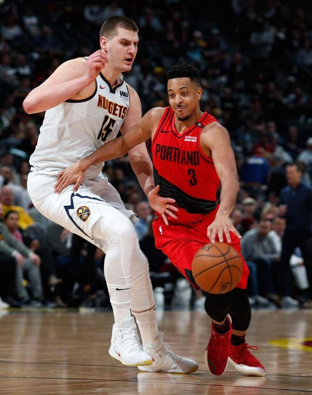 SMALL BUT TERRIBLE: Ang pointguard sa Portland Trail Blazers nga si  guard CJ McCollum, tuo, ang padulong na molusot bisan pa man sa hugot nga depensa sa higanting sentro sa Denver Nuggets nga si Nikola Jokic atol sa Game 2 sa ilang Western Conference semis kagahapon. (AP)