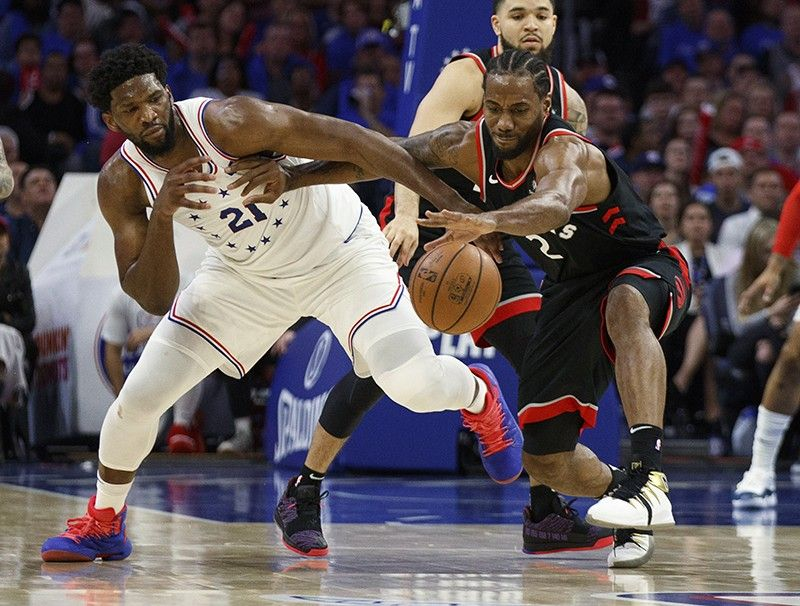 Toronto Raptors' Kawhi Leonard, right, reaches for the ball as he holds off Philadelphia 76ers' Joel Embiid, left, during the second half of Game 3 of a second-round NBA basketball playoff series Thursday, May 2, 2019, in Philadelphia. The 76ers won 116-95. <b>(AP Photo)</b>
