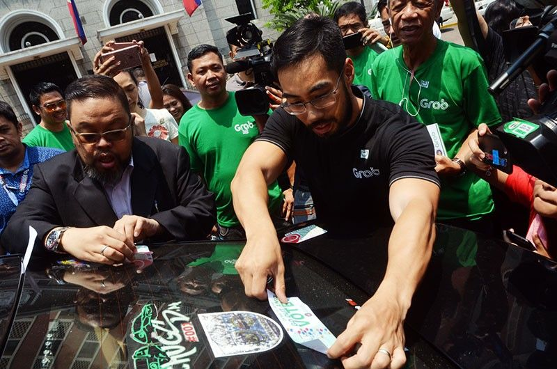 MANILA. Comelec spokesman James Jimenez (left) and Grab Philippines president Brian Cu place a