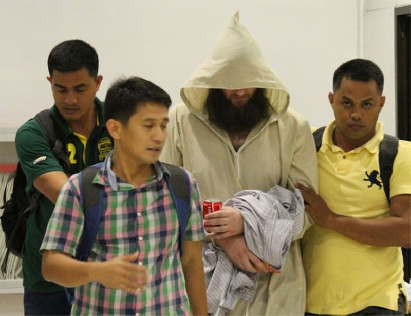 CEBU. Police operatives escort Australian national Robert Cerantonio, alias Musa, (second from right) upon their arrival at the Ninoy Aquino International Airport in Manila. (AP)