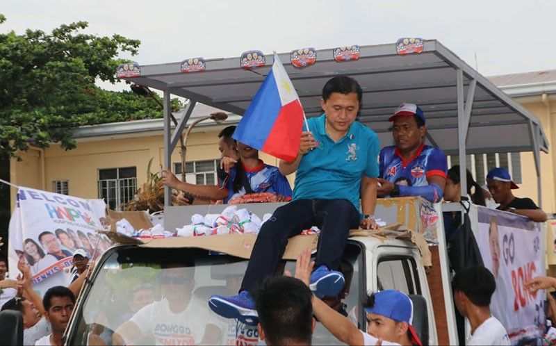 PAMPANGA. Senatorial candidate Christopher 'Bong' Go holds a miniature Philippine flag while on board a truck during Friday's motorcade in Pampanga. (Chris Navarro)