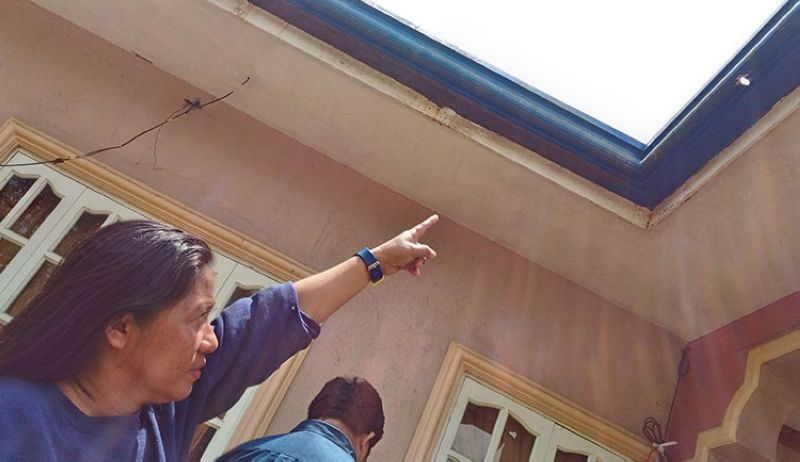 CEBU. Amor Cabiles, head of the barangay mayor's office in Sudlon 1, Cebu City, points to the bullet hole in her roof after her house was strafed last Saturday night, May 4. (SunStar/Amper Campana)