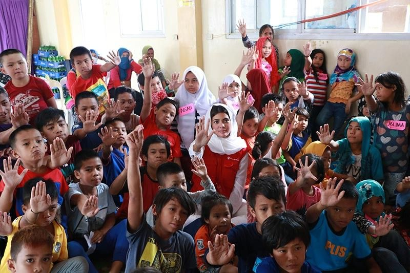 MARAWI. Miss World Philippines 2018, Katarina Rodriguez (center, wearing white hijab in red vest sitting), joins the children of Marawi City as they raise their right hands in support to Save the Children campaign: Stop the War Against Children. (Contributed photo)