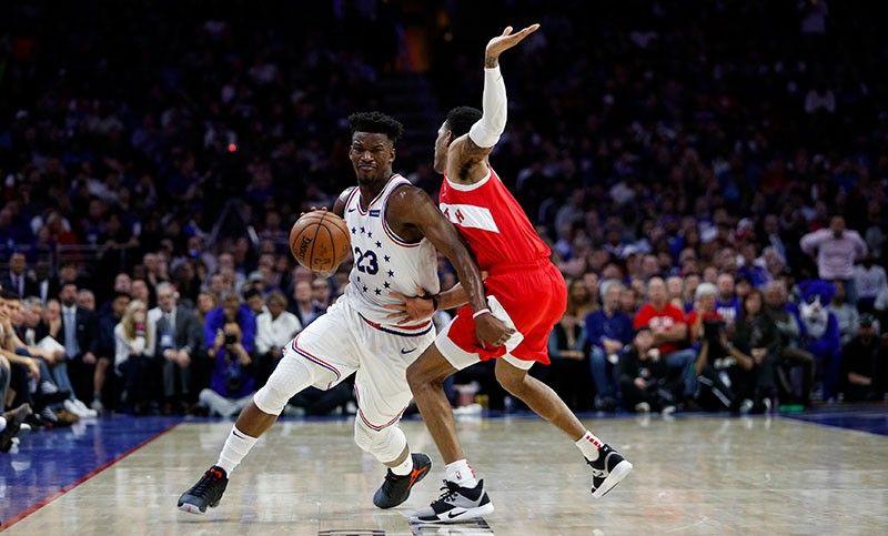 GILUTSAN. Si Jimmy Butler, wala, sa Philadelphia 76ers nga milighot sa depensa ni Patrick McCaw sa Toronto Raptors niining aktoha sa Game 6 nila kagahapon sa Eastern Conference semifinals. (AP)