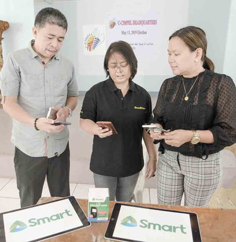 Media Linkage. DyLA station manager Jhunnex Napallacan and SunStar director of content Nini Cabaero (middle) inspect phones turned over by NN Navarro of Smart for the midterm election coverage.  Contributed Photo