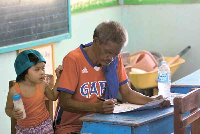 INHERENT RIGHT. In this file photo, a senior citizen votes inside a polling precinct while his grandchild waits for him to finish casting his vote. (SunStar File Photo)