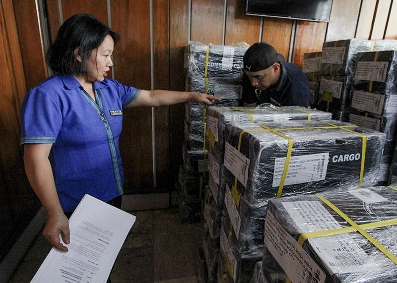 An employee of the Baguio City Treasurer's Office accounts ballots to make sure the identification number match today's national and local election. (Photo by Jean Nicole Cortes)