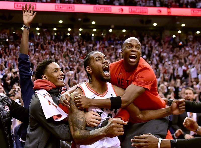 ANG BAYANI: Si Toronto Raptors forward Kawhi Leonard, tunga, nga nagselebrar uban sa iyang mga teammates human sa iyang bayanihong itsa sa himatyong segundos nga maoy nagpukan sa Philadelphia Sixers, 92-90, nga maoy naghatod kanila ngadto sa NBA Eastern Conference finals kagahapon. (AP)