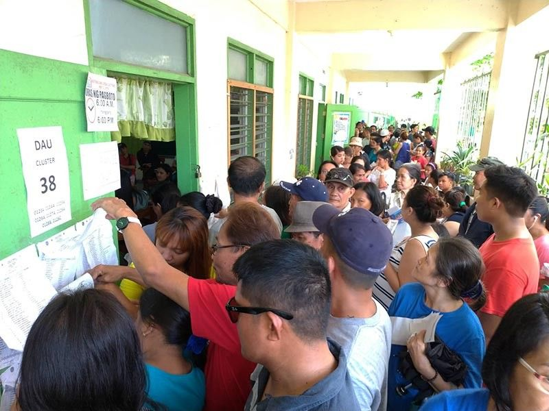PAMPANGA. Numerous voters in Dau Central Elementary School complain about long queues due to glitches of vote counting machines and paper jams. (Rey Navales)