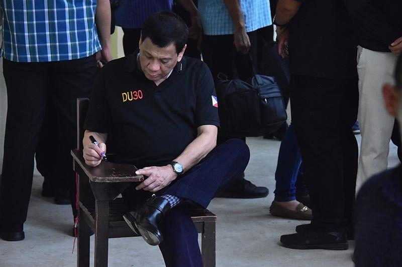 DAVAO. Si Pangulong Rodrigo Duterte milingkod sa kahoy nga armchair nga una niyang gilingkuran atol sa pagboto niya dihang nagpapili siya isip presidente ug iyang gilagdaan. (Hulagway ni Macky Lim)