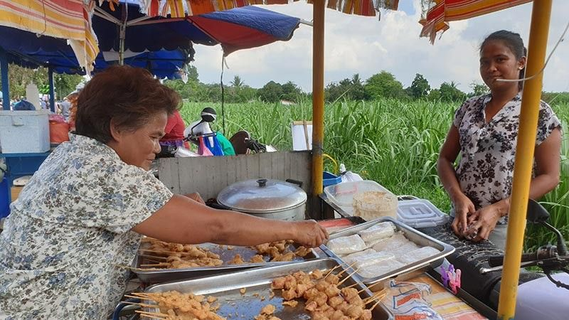 BACOLOD. Arlene and Mary Ann Tanique in their food cart. This is their own spicy concoction for their fried Isaw and chicken blood. (Carla N. Cañet)