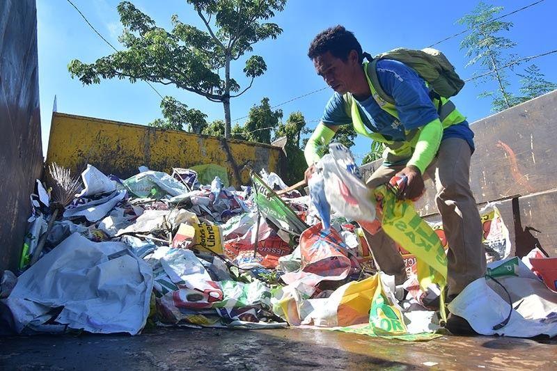 DAVAO. Makita kining usa ka sakop sa City Environment and Natural Resources Office sa Davao City nga okupado sa pag-segregate sa mga poster sa politiko nga dunay kahoy ug plastik atol sa Oplan Baklas kagahapon sa siyudad sa Davao. (Macky Lim)