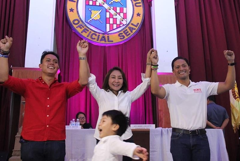NEW FACES IN CEBU'S 5TH DISTRICT. Rep. Gwendolyn Garcia (center) raises the hands of newly minted congressman Duke Frasco (right), her son-in-law, and Provincial Board member Red Duterte (left) of Cebu's fifth district after the two men had been proclaimed winners on Tuesday, May 14 at the Capitol Social Hall. The little photobomber is Garcia's grandson and Frasco's son. (SunStar photo / Amper Campaña)