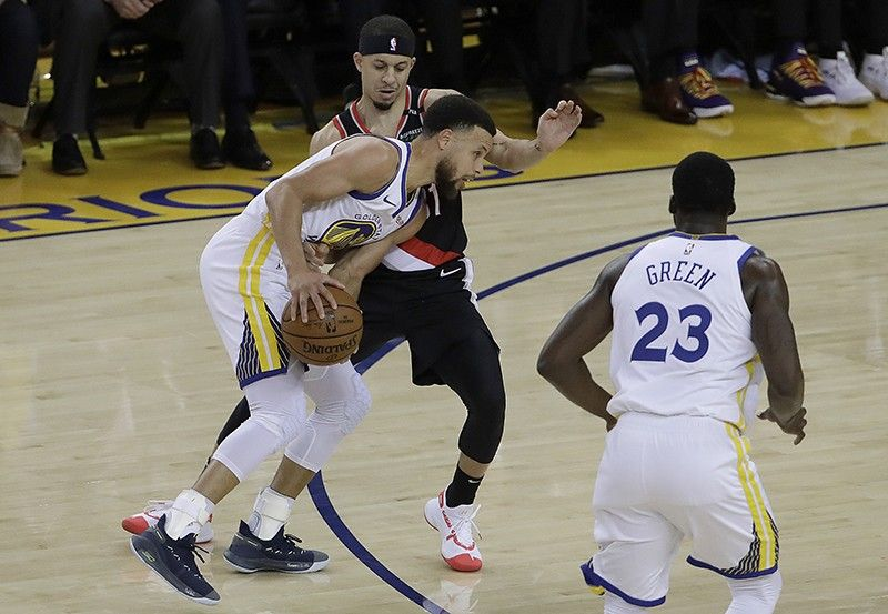 Golden State Warriors guard Stephen Curry, bottom left, is defended by Portland Trail Blazers guard Seth Curry during the first half of Game 1 of the NBA basketball playoffs Western Conference finals in Oakland, Calif., Tuesday, May 14, 2019. <b>(AP)</b>