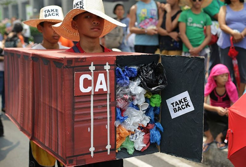 MANILA. In this May 7, 2015 photo, Filipino environmental activists wear a mock container vans filled with garbage to symbolize the 50 containers of waste that were shipped from Canada to the Philippines two years ago, as they hold a protest outside the Canadian embassy in Makati City. (AP)