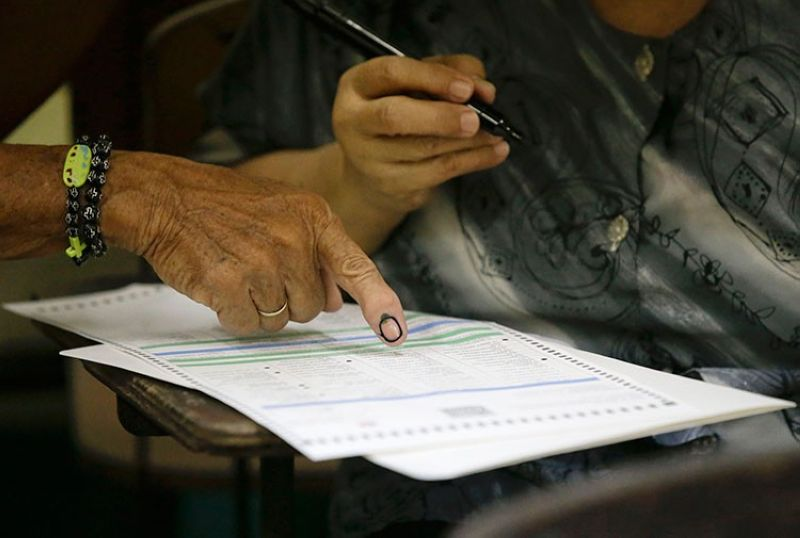 MANILA. A man helps his wife fill out her ballot as they vote at a polling center in the Manuel L. Quezon elementary school, Manila, Philippines, Monday, May 13, 2019. (AP)