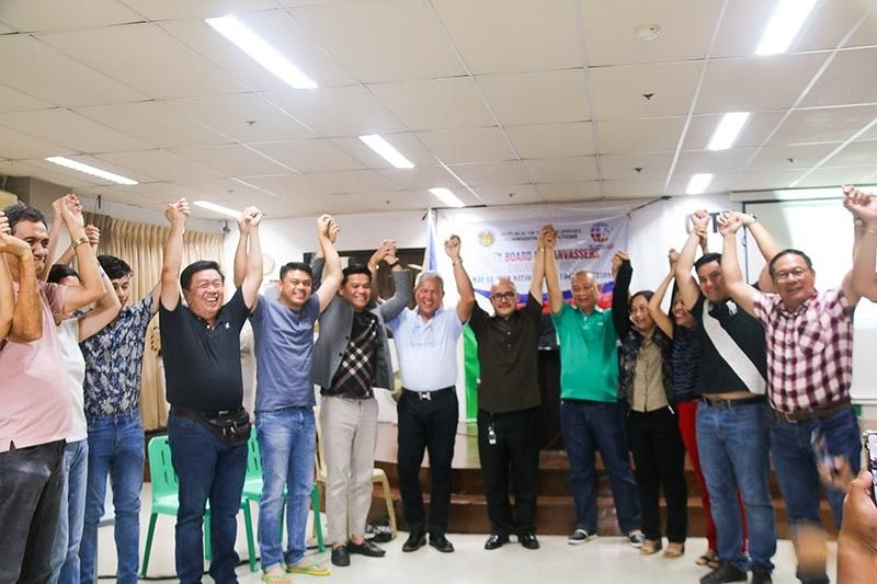 CAGAYAN DE ORO. Cagayan de Oro city election officer, Ramil Acol (center, brown coat), raises a hand of Mayor Oscar Moreno to formally proclaim him as the winning candidate for the mayoral race. Along with Moreno are winning vice mayor and city councilors who are allied with him under the local Partido Demokratikong Pilipino-Lakas ng Bayan. (Cyrill Garcia)