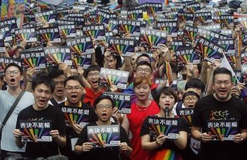 TAIWAN. Same-sex marriage supporters gather outside the Legislative Yuan in Taipei, Taiwan, Friday, May 17. Taiwan's Constitutional Court are scheduled to decide Friday on legalizing same-sex marriage, marking a potential first in Asia. The signs read  ''Vote Can't Be Defeated.'' (AP)