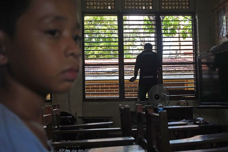 BACK TO SCHOOL. Clint Dave Rosacena, 11, doesn't look too happy, while his father cleans one of the classrooms at the Mandaue City Central School. (SunStar Photo/Allan Cuizon)