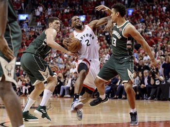 Toronto Raptors forward Kawhi Leonard (2) drives to the net against Milwaukee Bucks center Brook Lopez (11) and guard Malcolm Brogdon (13) during the second overtime period of Game 3 of the NBA basketball playoffs Eastern Conference finals in Toronto on Sunday, May 19, 2019. Toronto Raptors forward Kawhi Leonard (2) drives to the net against Milwaukee Bucks center Brook Lopez (11) and guard Malcolm Brogdon (13) during the second overtime period of Game 3 of the NBA basketball playoffs Eastern Conference finals in Toronto on Sunday, May 19, 2019. <b>(AP photo)</b>