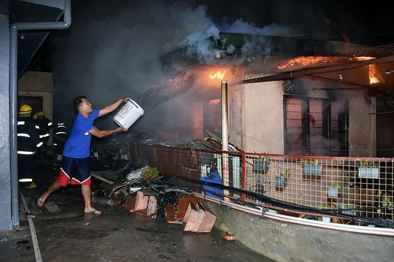 BAGUIO. A resident in Imelda Village Barangay help in putting out fire from a burning house using buckets of water at around 3 a.m. on Sunday. Fortunately no one was injured but investigation is still being conducted to know the damage and the cost of the fire incident. (Photo by Redjie Melvic Cawis)