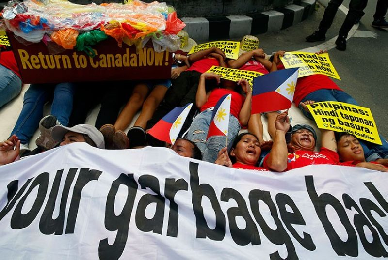 MANILA. Environmentalists stage a mock die-in protest outside the Canadian Embassy on May 21, 2019 to demand the Canadian government to speed up the removal of several containers of garbage that were shipped to the Philippines. (AP)