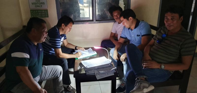 PAMPANGA. Despite the power interaption caused by heavy rains last Tuesday, May 21, DPWH-Pampanga 3rd District Engineering Office DE Tito Salvador (2nd L) and ADE Arnold Ocampo (2nd R) go through paperworks using a portable LED lamp. Looking on are Bacolor Mayor-elect Diman Datu (L) and other officials. (Chris Navarro)