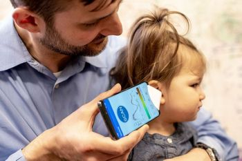 USA. In this undated photo provided by the University of Washington in May 2019, Dr. Randall Bly uses a uses a phone app and a paper funnel to focus the sound, to check his daughter for an ear infection, at the UW School of Medicine in Seattle. (AP)