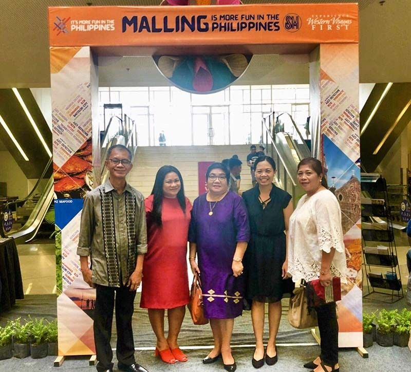 Department of Tourism (DOT)-Western Visayas Regional Director Helen Catalbas (center) with Provincial Supervising Tourism Operations officer Cristine Mansinares (second from right), Alphonsus Tesoro of Capiz Tourism and Cultural Affairs Office (left), Lorna Longno of Smallville Travel and Tours (second from left), and Lilibeth Traspadillo of Negros Occidental Tourism Division at the sidelines of the ongoing