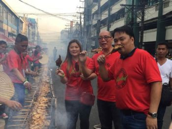 (From right) Lone District of Bacolod Representative Greg Gasataya, Vice Mayor El Cid Familiaran and Councilor Cindy Rojas also get a taste of the grilled chicken showcased during the Second Chicken Inasal Festival held at Araneta Street over the weekend. (Merlinda Pedrosa)  onerror=