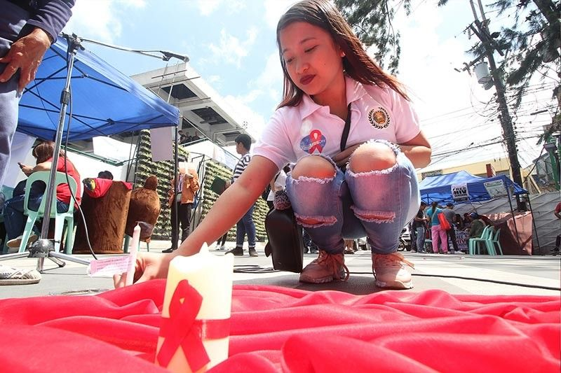 BAGUIO. Entertainers in the different night establishments in Baguio City join the candle lighting at the People's Park on May 24 to commemorate aids victims and spread awareness about the sexually transmitted disease. (Jean Nicole Cortes)