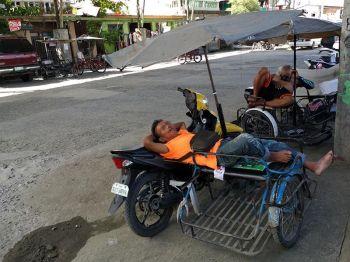 Naglumbaanay og tulog ang duha ka drayber sa ilang mga payong-payong kilid sa dagat tungod sa bugnaw nga huyuhoy sa hangin gikan sa baybayon sa Barangay 76-A Bucana, Davao City, Lunes sa buntag, Mayo 27. (Macky Lim)