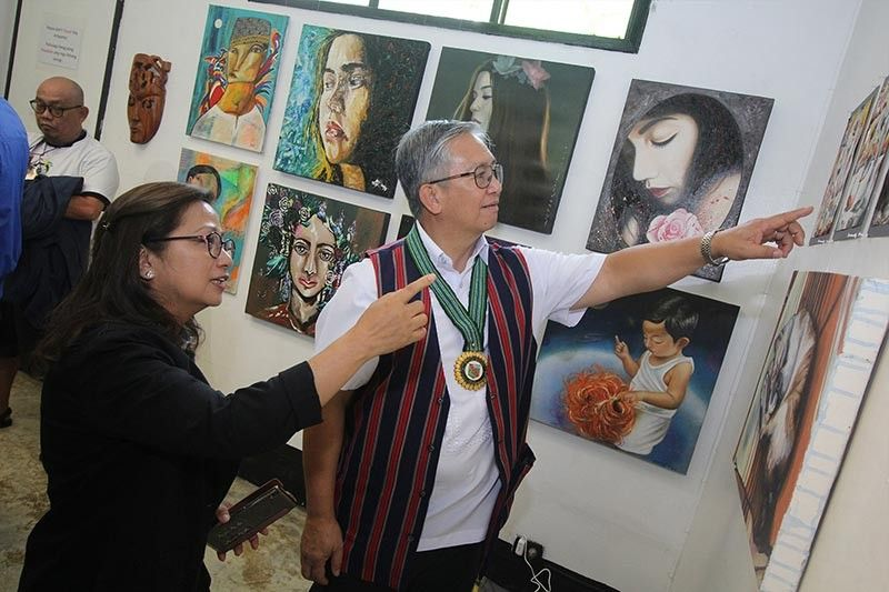 BAGUIO. Benguet Governor Crescencio Pacalso and Baguio Councilor Mylene Yaranon take a look at the artwork made by artists from all over the Philippines during the Tam-awan International Arts Festival. (Jean Nicole Cortes)