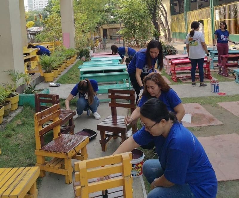 SHOWING KINDNESS. SM City Cebu employee-volunteers join the Brigada Eskwela by repainting the tables and chairs in Mabolo Elementary School. (Contributed photo)