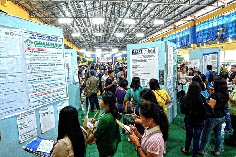 COMPETING FOR JOBS. Applicants at a jobs fair check a list of vacancies. Among the Philippines' strengths in IMD's World Competitiveness Rankings is its labor pool. (SunStar file)