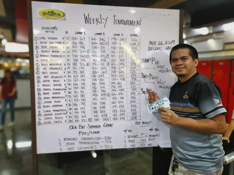 I AM THE WINNER. Datba weekly Mike Aquiatan poses beside the scoreboard at SM Lanang Premier Bowling Center Tuesday evening. (AJ Galendez Facebook)