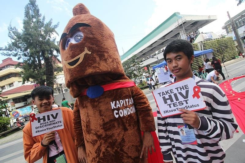 "BAGUIO. Aids advocates and the Department of Health's mascot ""kapitan condom"" promotes safe sex and calls on the public to get tested for the sexually transmitted disease. (Photo by Jean Nicole Cortes)"