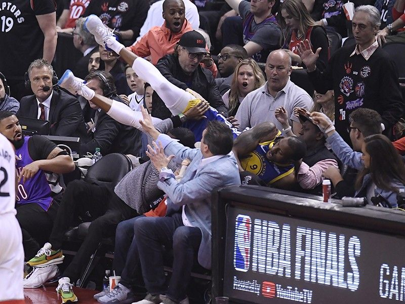 Golden State Warriors guard Andre Iguodala falls into the stands during the first half of Game 1 against the Toronto Raptors in basketball's NBA Finals, Thursday, May 30, 2019, in Toronto. <B>(AP)</B>