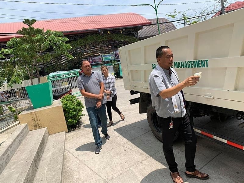 PAMPANGA. Reverend Father Roland Moraleja, parish priest of Masantol town, blesses the new garbage truck purchased by the local government recently. Witnessing the rites are Vice Mayor-elect Boboy Lacap, Mayor's Office administrative aide Arian Ignacio and Office of Senior Citizens Affairs officer Johnny Balingit. (Photo by Princess Clea Arcellaz)