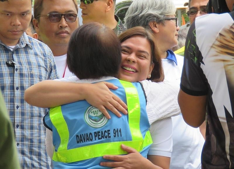 DAVAO. Mayor Sara Z. Duterte-Carpio gives City Adviser for Peace Irene M. Santiago a tight hug while thanking her for the gains achieved in Paquibato over a period of one year during the mayor's arrival for the 1st anniversary celebration of Davao City's Peace 911, a local initiative to put an end to communist insurgency. (Photo by Stella A. Estremera)
