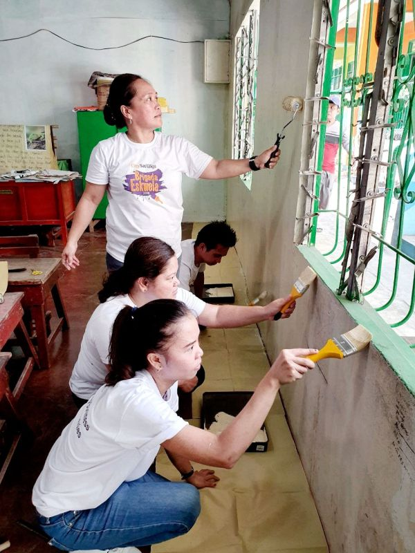 NEW PAINT ON THE WALL. Employees of City Savings Bank paint a classroom in a barangay in Mactan, Cebu during Brigada Eskwela. (Contributed foto