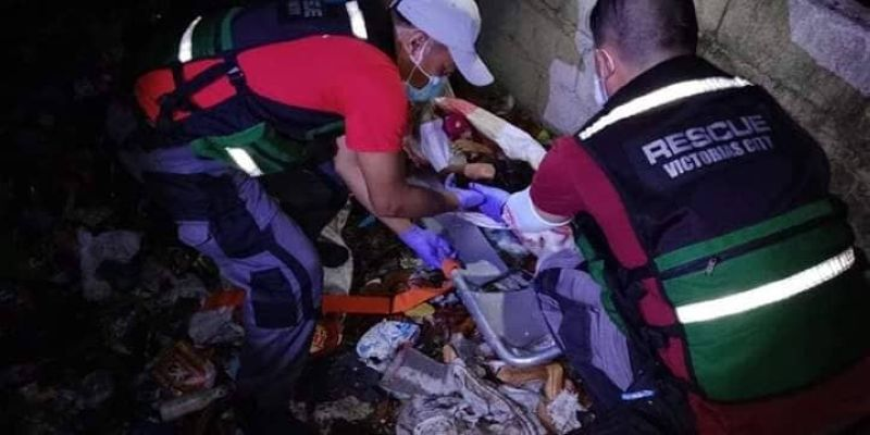 NEGROS. Rescuers help retrieve the body of the seven-year-old girl who was found inside a sack at a vacant lot in Barangay 6-A, Victorias City Sunday night. (Photo by CDRMMO Victorias)
