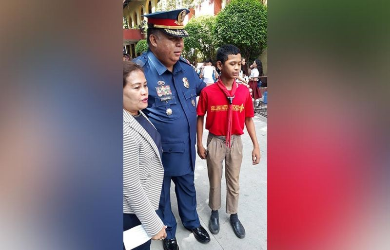COMMUNITY OUTREACH. During a visit to the Abellana National School, Police Regional Office 7 Director Debold Sinas takes time out from checking security to chat with students and pose for souvenir photos. (SunStar photo / Arnold Bustamante)