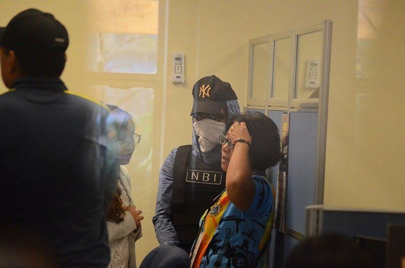 NASAYPAN NGA SUSPEK: Sa tunga mao ang nasaypan nga unang suspek nga menor de edad sa pagpatay ni Christine Lee Silawan nga kanhi gitanggong sa National Bureau of Investigation (NBI). (Alan Tangcawan)