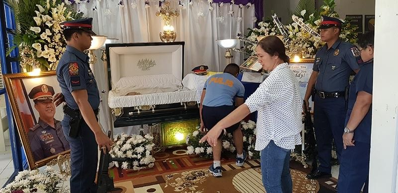 CAGAYAN DE ORO. Police officers and staff inside the headquarters of Cagayan de Oro City Police Office in Barangay 40 arrange Thursday, June 6, the flowers around the coffin where the late Police Colonel Nelson Aganon's body is resting. (Nef Luczon)