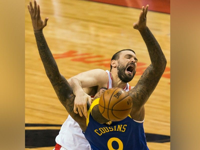 Toronto Raptors center Marc Gasol, top, loses control of the ball under pressure from Golden State Warriors centrer DeMarcus Cousins (0) during first-half basketball action in Game 5 of the NBA Finals in Toronto, Monday, June 10, 2019. (AP)