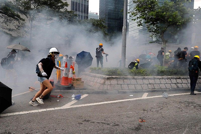 HONG KONG. Protesters react to tear gas during a large protest near the Legislative Council in Hong Kong, Wednesday, June 12, 2019. Hong Kong police have used tear gas and high-pressure hoses against thousands of protesters opposing a highly controversial extradition bill outside government headquarters. (AP)