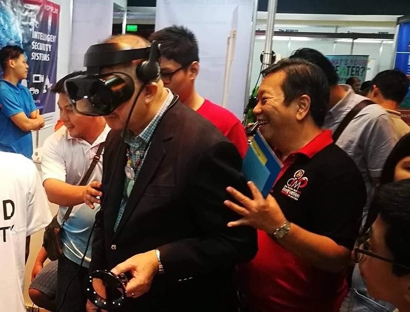 NEW LEVEL OF EXPER-IENCE: Science and Technology Secretary Fortunato dela Peña (left)tries on the virtual reality technology during his visit at the opening of the 2019 Cebu Innovation Expo. With him is Felix Taguiam (right) the 2019 Cebu Business Month adviser. (SunStar photo / Allan Cuizon)