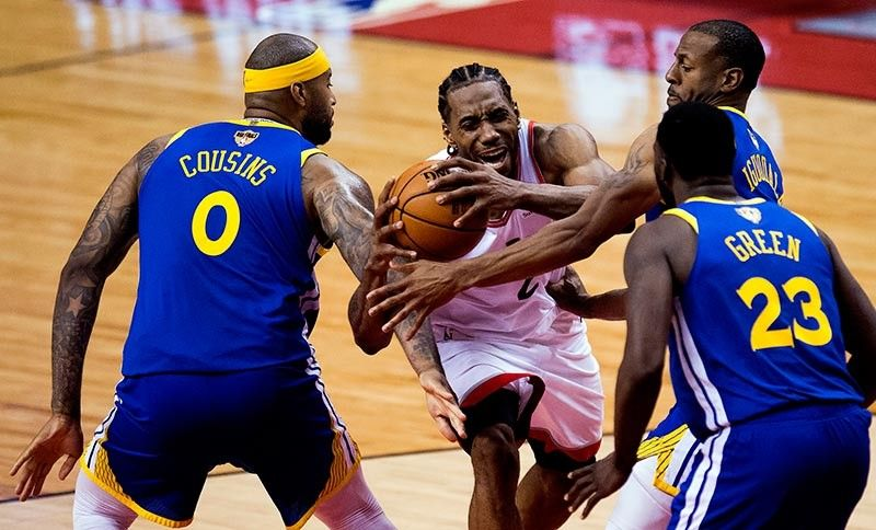 TRIPLE-TEAM. Toronto Raptors forward Kawhi Leonard (2) draws a foul as he drives to the net against Golden State Warriors center DeMarcus Cousins (0), forward Draymond Green (23) and forward Andre Iguodala (9) during second-half basketball action in Game 5 of the NBA Finals in Toronto, Monday, June 10, 2019. (Chris Young/The Canadian Press via AP)