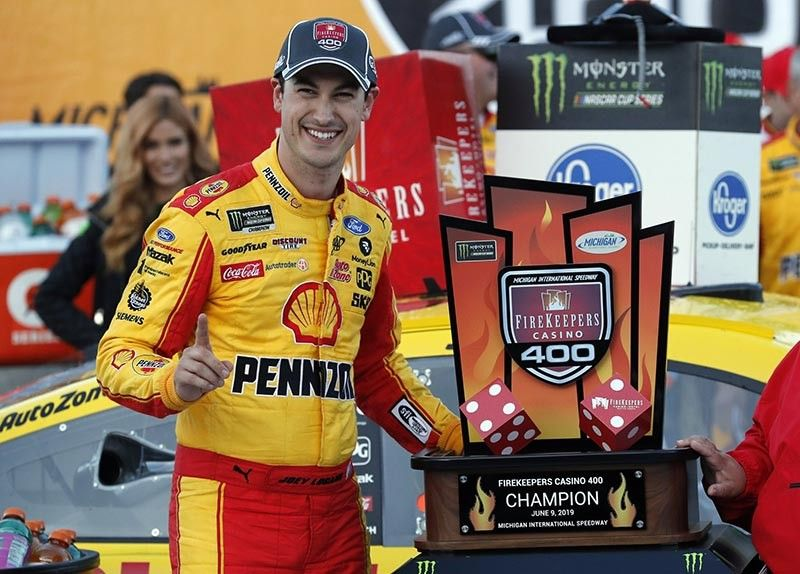 Joey Logano stands with the trophy after winning a NASCAR Cup Series auto race at Michigan International Speedway, Monday, in Brooklyn, Michigan. (AP Photos)